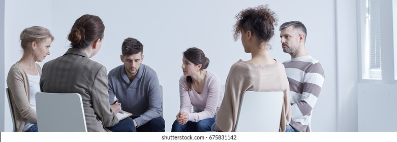 Meeting of support group talking about problems sitting in circle
