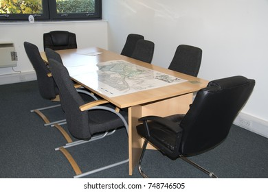 meeting table with black chairs in an office room