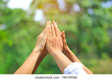 Meeting teamwork concept,Friendship,Group people with stack of hands showing unity on natural green background