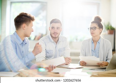 Meeting of three young professionals with papers sitting by table and discussing information