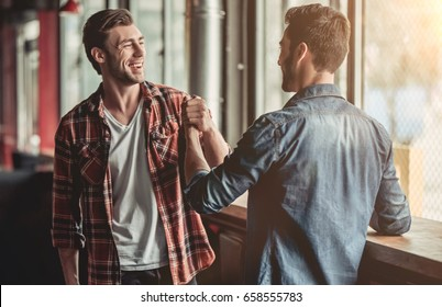 Meeting of two handsome male friends in bar.