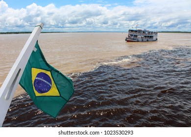 Meeting of the Waters of Rio Negro and the Amazon River or Rio Solimoes near Manaus, Amazonas, Brazil in South America with waving Brazil flag
