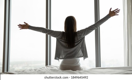 Meeting wonderful day. Rear view of inspired excited millennial woman sitting on bed in comfortable hotel room modern designed flat apartment outstretching arms in delight looking forward perfect rest