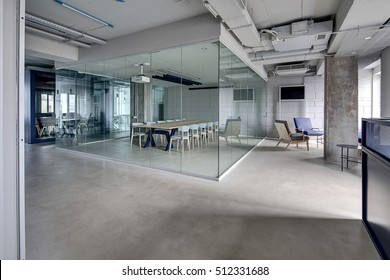 Meeting zone in the office in a loft style with white brick walls and concrete columns. Zone has a large wooden table with gray chairs and glass partitions. Above the table there is a projector.