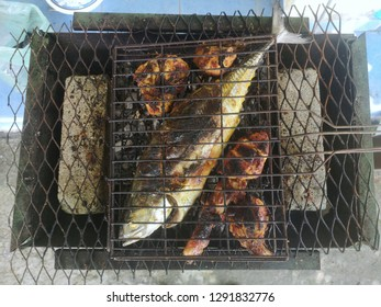 The 'Megalaspis cordyla' fish roasted on fire with chicken slices outdoor.