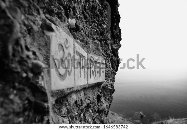Meganom, Crimea / Russia - 10.30.2019: A plate with the Hindu mantra Om Namah Shiva on a stone surface of a cliff close-up, sea scape background.
