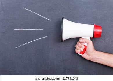 Megaphone . Close-up of human hand holding megaphone against blackboard