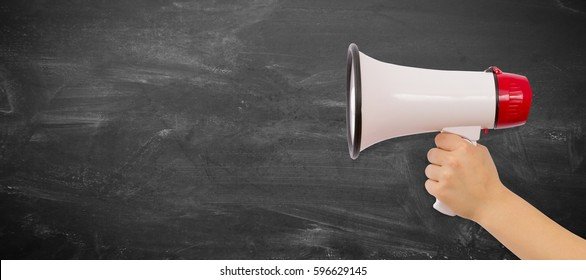 Megaphone. Close-up of human hand holding megaphone against blackboard