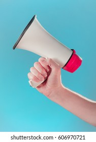 Megaphone in hand blue background. Audio proclamation concept.