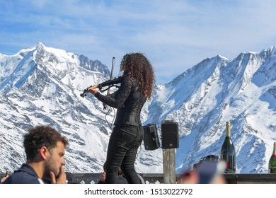 Megeve, Chamonix /  France - March 15 2017: Violinist woman with black dress and curly hair playing violin at La Folie Douce Saint Gervais Restaurant, France. Snow capped Mont Blanc in the background.