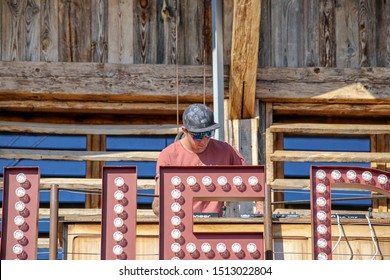 Megeve, France - March 14 2017: DJ with baseball cap and sunglasses performing with his mixer on a wood stage. From the La Folie Douce Saint Gervais Restaurant Apres Ski Party