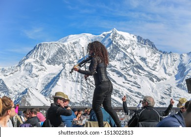 Megeve, France - March 15 2017: Violinist woman playing violin at after ski restaurant. Snow capped Mont Blanc in the back on a sunny winter day. La Folie Douce Saint Gervais Restaurant in Chamonix.
