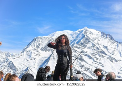 Megeve, France - March 15 2017: Violinist woman greets audience with her violin. Snow capped Mont Blanc in the background on a sunny winter day. La Folie Douce Saint Gervais Restaurant at Chamonix.