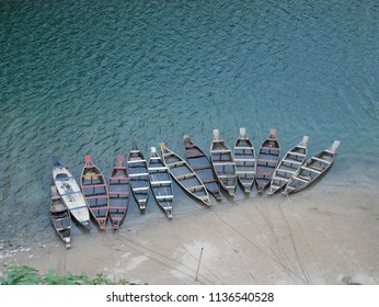 Meghalaya, India - June 3, 2018 - Tourist boats line a sand spit along the Umngot River on Bangladesh's northern border with India.