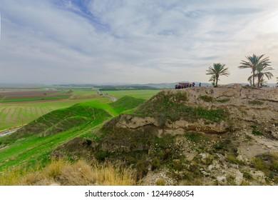 Megiddo, Israel - November 29, 2018: Tourists visiting the Tel Megiddo National Park, and Landscape of the Jezreel Valley. Northern Israel