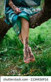 mehendi on the feet and feet of a girl sitting on a tree branch