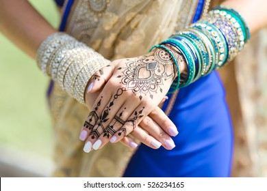 mehendi on the hands of girls,Woman Hands with black mehndi tattoo. Hands of Indian bride girl with black henna tattoos. Hand with perfect turquoise manicure and national Indian jewels. Fashion. India