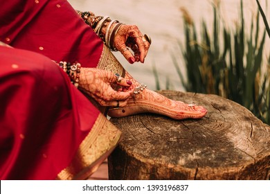 mehendi on the legs of the bride, mehendi on the legs of a girl in a red sari, hands and feet of Indian bride's mehendi