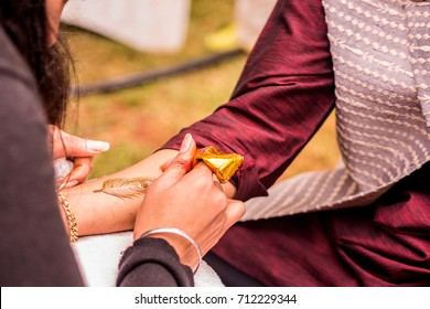 Mehndi artist carefully painting an intricate design using henna, on the forearm of  Indian bridegroom before a Vivaah-Indian Wedding. Arm resting on white towel. Gold tube of henna. Feather design.