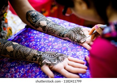 Mehndi artist making mehndi design women hands