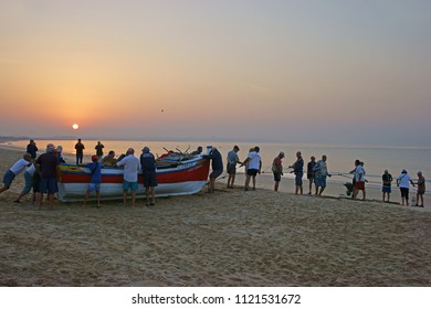 Meia Praia, Lagos, The Algarve, Portugal, June, 23rd, 2018, many  fishermen and women launching the Jose Fernando, LC 1155-L at sunrise from Meia Praia into the Bay of Lagos to lay fishing nets.