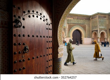 Meknes, Morocco - December 9, 2015:  People with djellaba walking front of Bab Mansour gate, view from inside a entry hall of a classical building. Bab Mansour gate is the largest in North Africa.