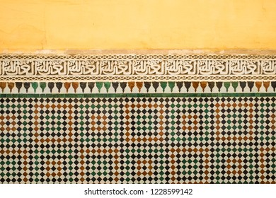Meknes, Morocco. March 17, 2014 : Colourful old Moroccan yellow painted wall with a band of Islamic calligraphy above zellige tilework.