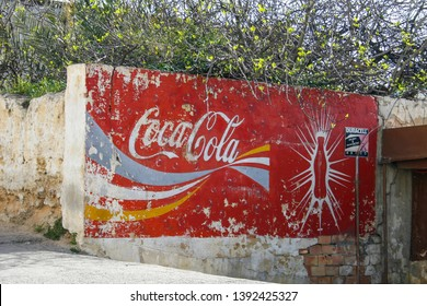 Meknes, Morocco - March 3 2019 - A vintage, fading, large, painted sign advertising Coca Cola.