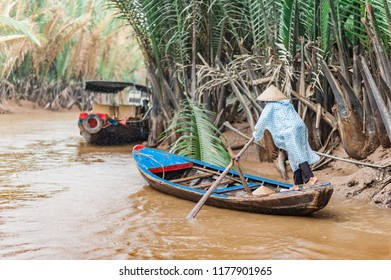 Mekong Delta, Ben Tre, Vietnam - October 21, 2016. Local woman rowing a traditional boat along the canals through the Mekong River Delta in Vietnam. Muddy tropical waters surrounded by lush mangroves.