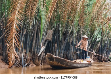 Mekong Delta, Ben Tre, Vietnam - October 21, 2016. Local man rowing a traditional boat along the canals through the Mekong River Delta in Vietnam. Muddy tropical waters surrounded by lush mangroves.