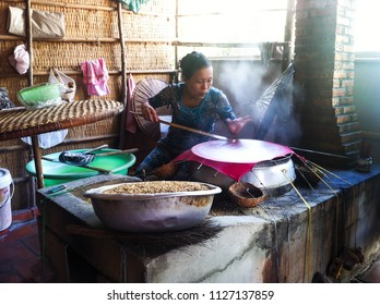 MEKONG DELTA, VIETNAM, - DECEMBER, 16, 2013: Vietnamese woman cooking rice paper on a traditional oven in a local marketplace