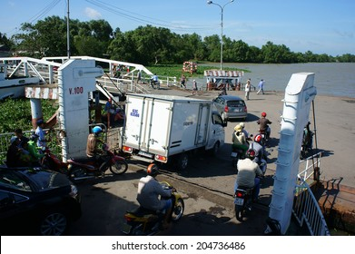 MEKONG DELTA, VIETNAM- JULY 7: Crowd of people wear helmet sitting on motorbike to cross the river by ferry boat, this is  passenger transport vehicle on water at My Loi ferry, Viet Nam, July 7, 2014