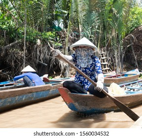 Mekong Delta, Vietnam - September 27, 2018: Vietnamese woman wearing a conical straw hat or non la while paddling a wooden tourist boat in the Mekong Delta.