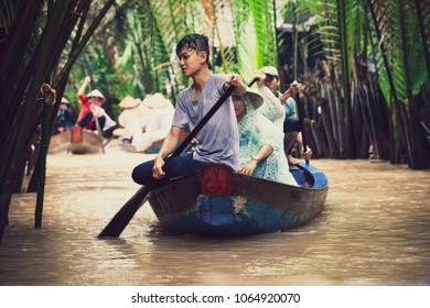 MEKONG, VIETNAM. August 05, 2017: Some Vietnamese people paddling on a small wooden boat in the famous Mekong river in Vietnam.