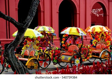 Melacca, Malaysia - December 27, 2006:   A row of colourful tri-shaw taxis decorated with plastic flowers parked in front of 1753 Christ Church await fares