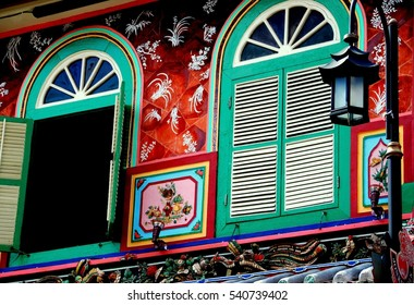 Melacca, Malaysia - December 27, 2006:  Hand-painted facade of a Nyonya heritage house on Jonker Walk with arched windows featuring large fans and louvered shutters