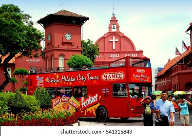Melacca, Malaysia - December 30, 2006: Double-decker touring bus in Stadthuys Square with historic clock tower, 1753 Christ Church Melaka, and Dutch Stadthuys (Town Hall)
