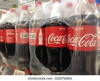 MELAKA, MALAYSIA - 2 JANUARY 2018: Plastic bottles of Coca Cola on shelves. Coca Cola company is leading soda drinks manufacturer in the world.