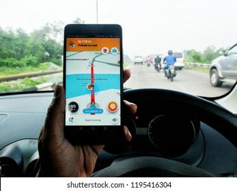 Melaka, Malaysia - Circa February, 2018: A bokeh picture of Waze showing slow traffic and warning of pothole on the road in the morning. Waze has gain popularity for its good navigation.""