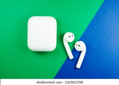 Melaka, Malaysia - Circa February, 2019: Apple AirPods wireless Bluetooth headphones and charging case for Apple iPhone on a black background. New Apple Earpods Airpods and box.
