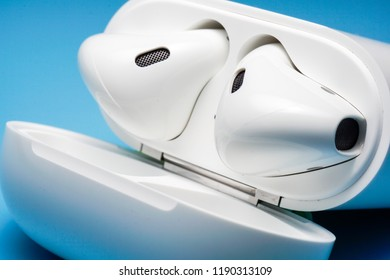 Melaka, Malaysia - Circa September, 2018: Apple AirPods wireless Bluetooth headphones and charging case for Apple iPhone on a blue background. New Apple Earpods Airpods and box.
