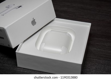 Melaka, Malaysia - Circa September, 2018: Apple AirPods wireless Bluetooth headphones and charging case for Apple iPhone on a black background. New Apple Earpods Airpods and box.