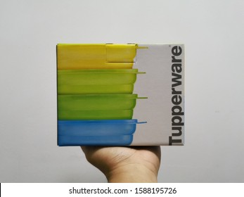 Melaka, Malaysia - December 14, 2019: a hand holding a Tupperware box against white wall background.