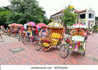MELAKA, MALAYSIA - FEB 10: Trishaw decorated with colorful flowers waiting for customer in Malacca, Malaysia on February 10, 2013. Malacca city is a designated UNESCO world heritage site