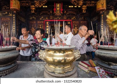 Melaka / Malaysia – February 20, 2018: People of Chinese ethnicity praying with incense sticks in Taoist temple located in Malaysia during Chinese new year