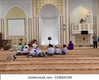 MELAKA, MALAYSIA- MARCH 1, 2019: Unidentified Muslim man in sits down in solat position Masjid Al Ghaffar Jasin, Melaka. Muslims compulsory to pray (solat) 5 times a day.