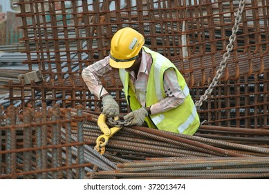 MELAKA, MALAYSIA � MAY 26, 2015: A construction worker hoisting the steel reinforcement bar at the construction site. The reinforcement bar was lifting using a crane.