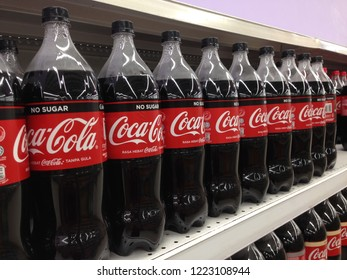 Melaka, Malaysia - November 6, 2018 : Coca-cola in bottles on row display for sale in the supermarket shelves. Coca-Cola is a carbonated soft drink produced by The Coca-Cola Company.