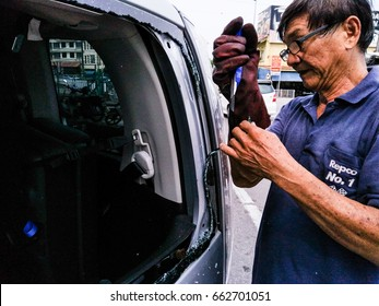 Melaka/Malaysia: 17th June 2017- A skillful man is fixing a broken rear window on a car due to road accident.
