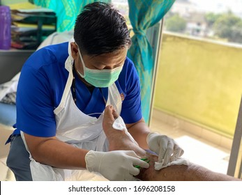 Melaka/Malaysia - April 7,2020 : A nurses doing wound dressing and debridement to remove any non viable tissue on the wound